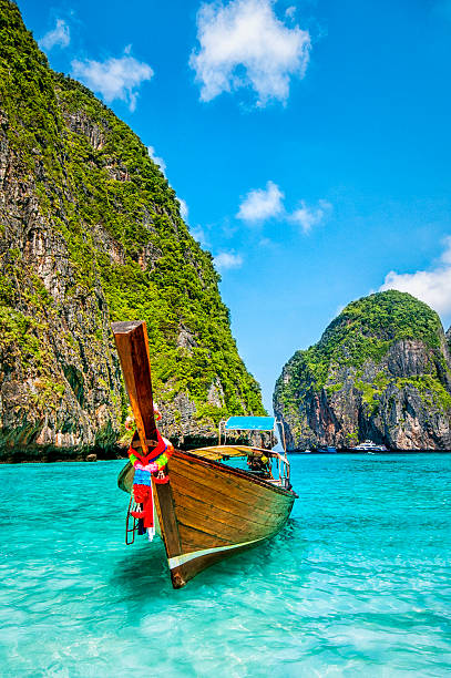 longtail wooden boat at maya bay, thailand - phuket stock photos and pictures