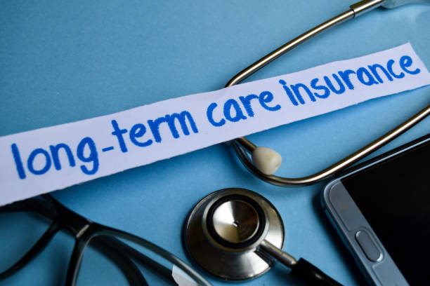 long-term care insurance inscription with the view of stethoscope, eyeglasses and smartphone on the blue background - long stock pictures, royalty-free photos & images