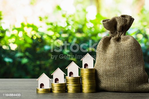 1145921132istockphoto Long-term property investment concept. Home loan, mortgage reverse. Saving money for buy new home. A small house on stack of coins and money bag on table. Depicts investing in sustainable real estate. 1164884433