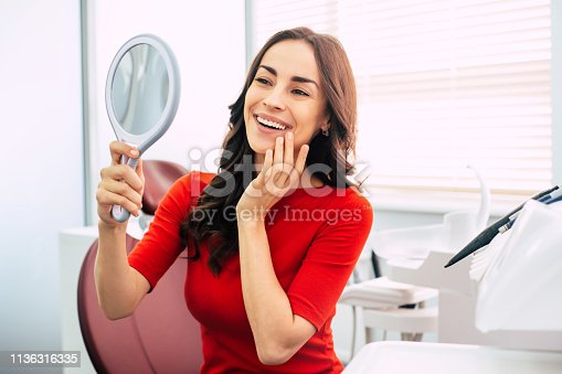 istock Long-term result. Nice looking girl in scarlet sweater is holding a mirror in her elegant hand and looking through the perfect  result of the dental work. 1136316335