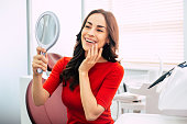 Nice looking girl in scarlet sweater is holding a mirror in her elegant hand and looking through the perfect  result of the dental work.