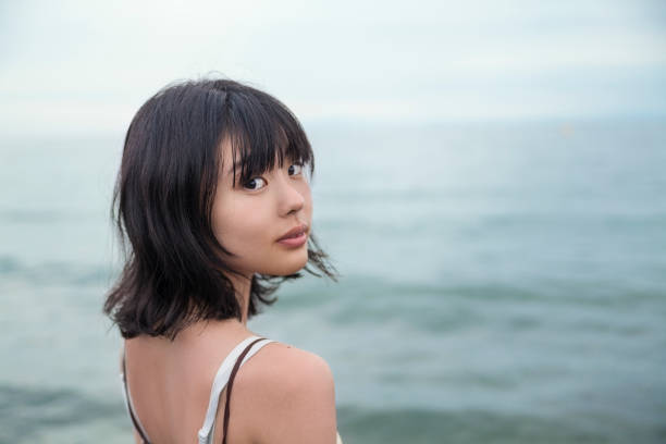 Lonly Young Woman By The Sea A lonely Japanese woman is looking at the camera over her shoulder by the sea. looking over shoulder stock pictures, royalty-free photos & images
