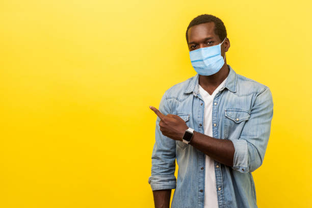 Look, advertise here! Portrait of positive man with surgical medical mask pointing left side and smiling at camera, showing empty space for advertise. stock photo