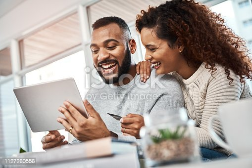 Shot of a young couple using a credit card and digital tablet at home