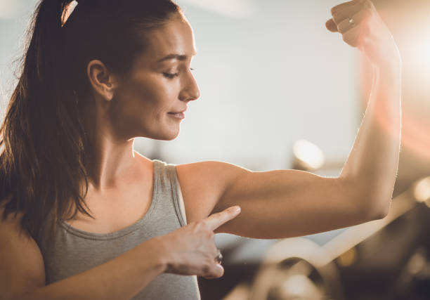 Look at my biceps! Smiling sportswoman flexing her muscles in a health club and aiming at her biceps. flexing muscles stock pictures, royalty-free photos & images