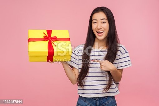 Look at my birthday present! Glad satisfied pretty girl with brunette hair in striped t-shirt pointing at gift box and smiling to camera, celebrating holidays. studio shot isolated on pink background