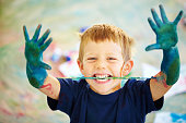 Cute little boy showing you his hands while covered in paint