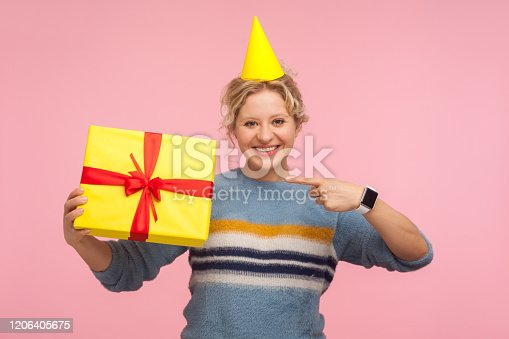 Look at my present. Portrait of happy woman with funny cone hat on head and in warm sweater pointing at holiday gift and smiling joyfully, showing birthday surprise. indoor studio shot pink background