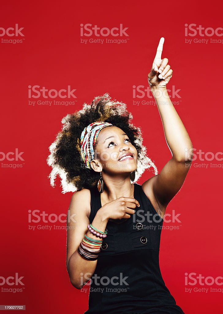Look at that! Afro-haired woman points up toward blank space royalty-free stock photo