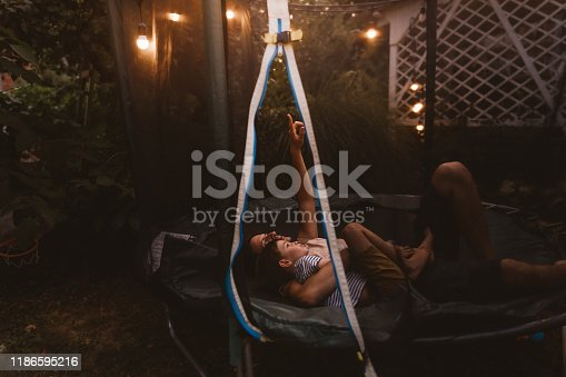 Photo of father and son lying together on a trampoline, looking up at the sky