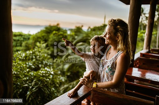 Happy little boy pointing at something in the distance while enjoying on balcony with his mother during summer day.