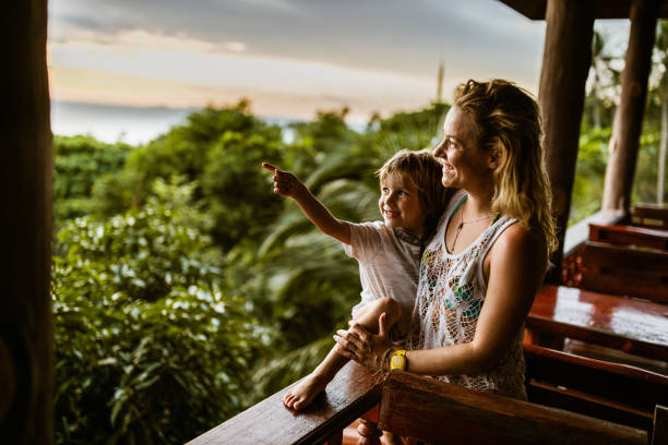 Look at that view, mom! Happy little boy pointing at something in the distance while enjoying on balcony with his mother during summer day. indochina stock pictures, royalty-free photos & images
