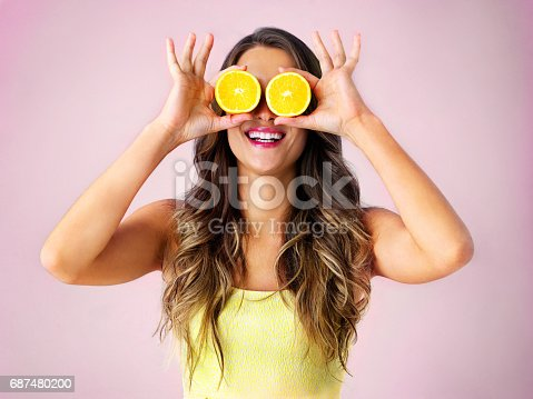 Studio shot of a young woman holding up two halves of a orange in front of her eyes