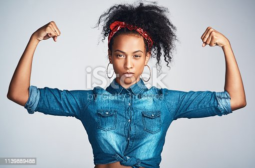 Portrait of a confident young woman wearing denim clothes and looking strong while flexing her biceps against a grey background