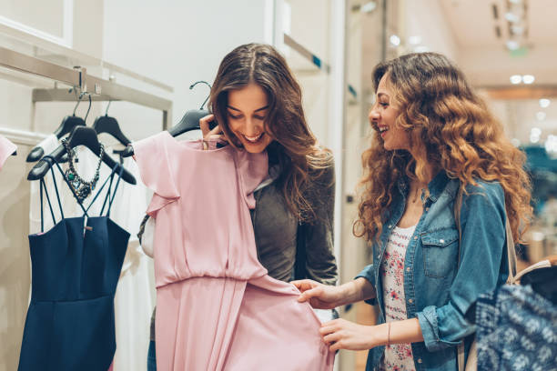 Look at this gorgeous dress! Two young women choosing dresses in a luxury fashion store dress stock pictures, royalty-free photos & images