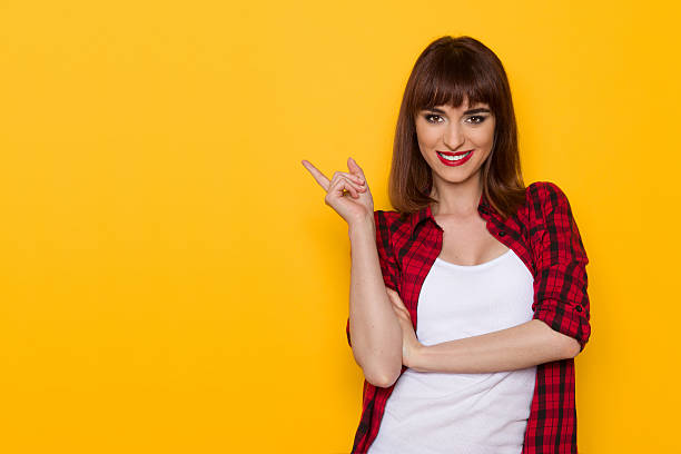 Look At This Yellow Copy Space Smiling young woman in unbuttoned red lumberjack shirt pointing away. Waist up studio shot on yellow background. plaid shirt stock pictures, royalty-free photos & images