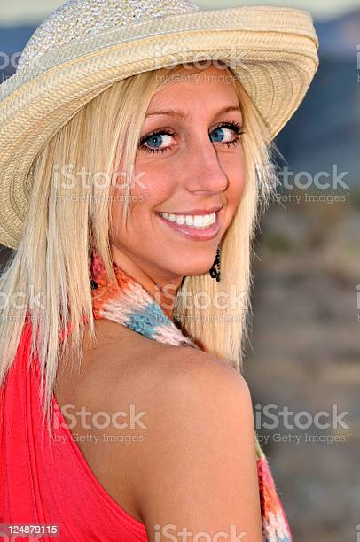 Beautiful Woman.  Gorgeous Eyes and A Winsome Smile.  Wearing Straw Hat & A Wrap.  Close Up.  Shallow Depth of Field. Low Light Shot.
