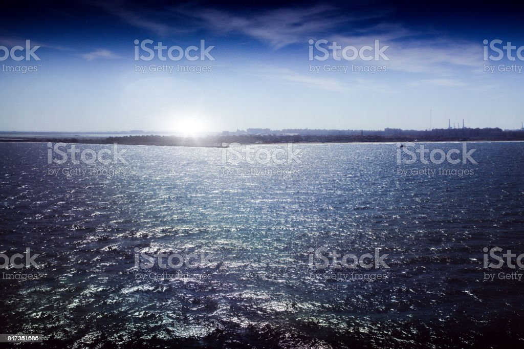Look back to Port Said and the entrance to the Suez Canal in backlight with light reflex stock photo