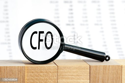 Closeup on businessman holding a card with text CFO, business concept image with soft focus background. Magnifying glass on the background of columns of numbers.