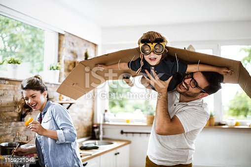 Happy boy pretending to be an airplane and looking at camera while his father is holding him in dining room.