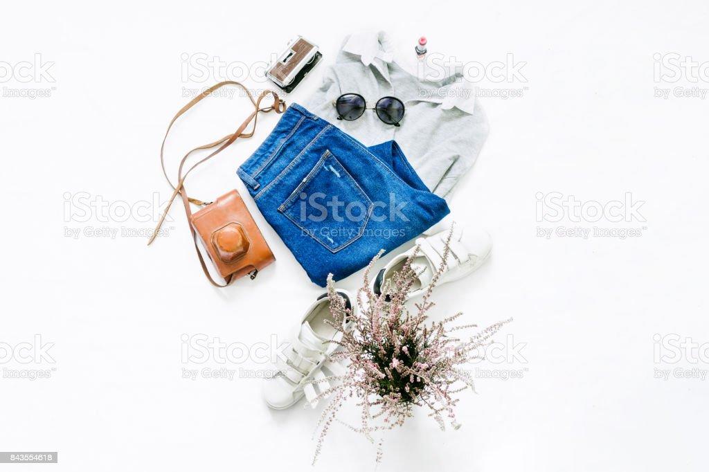白の背景に女性の服を見てください。ジーンズ、口紅、サングラス、白い背景に白いスニーカーと女性のポロ。美容ブログのコンセプトです。フラットを置く ストックフォト