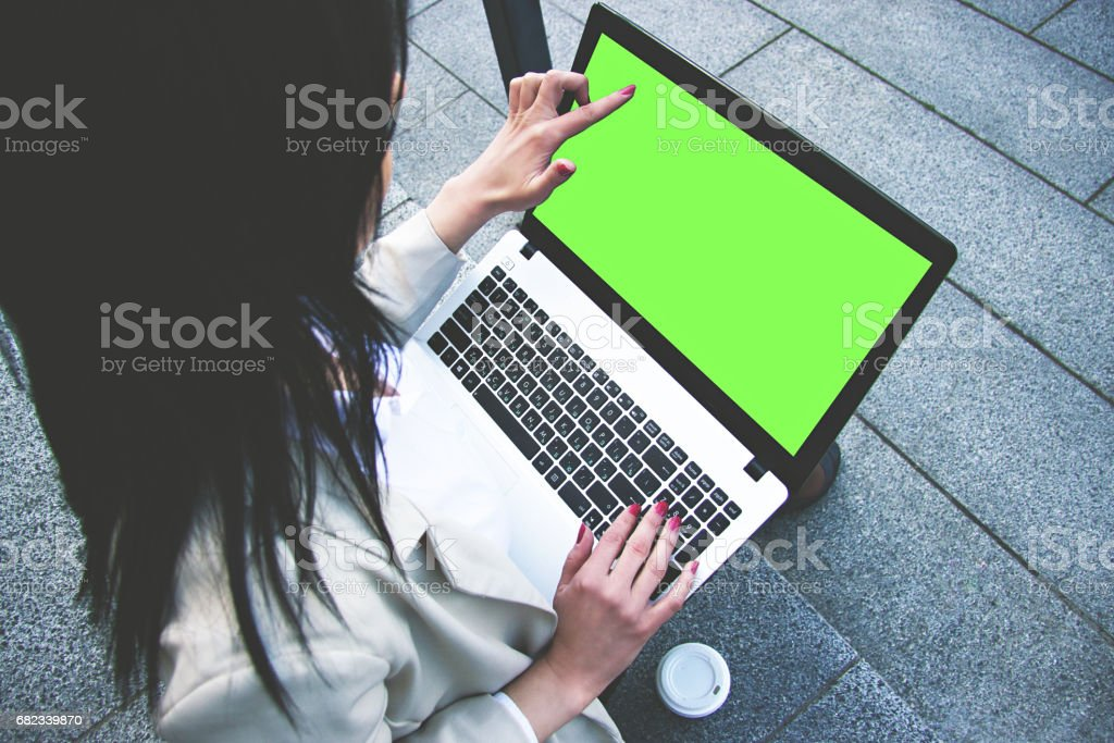 Look here. High angle view of attractive business woman in smart casual wear pointing at laptop's green screen and typing text on keyboard while working on laptop outdoors. Chroma key laptop. foto stock royalty-free