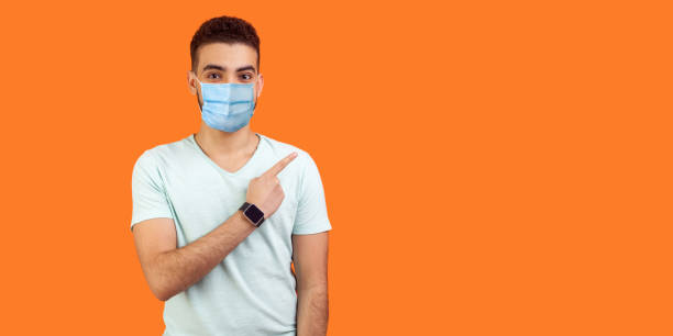 Look here! Portrait of brunette man with medical mask in casual white t-shirt standing pointing at left, empty space for text, advertise. stock photo
