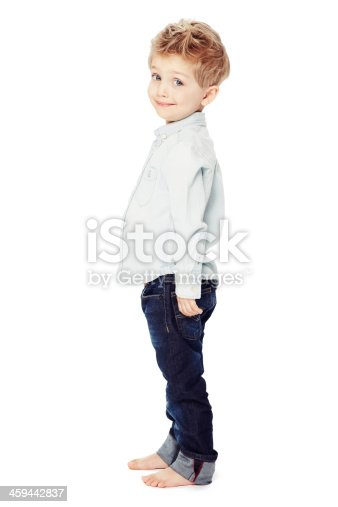 Side view of a cute little boy standing against a white background - portrait