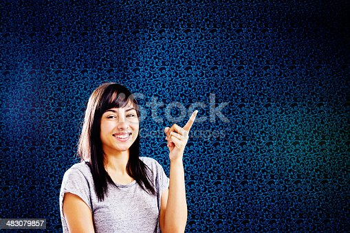 A sweet-looking, smiling young woman with long, dark hair points upwards, indicating an empty space for your product or message. Copy space on the patterned background.