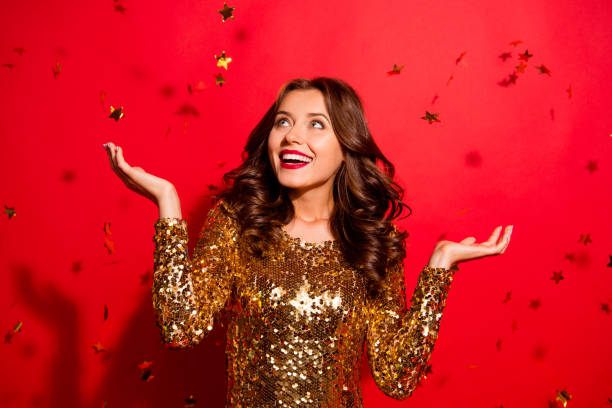 Look like fall stars from the sky! Lady with big white beaming smile look aside stand with modern wave hairdro isolated on vivid red background win winner Look like fall stars from the sky! Lady with big white beaming smile look aside stand with modern wave hairdro isolated on vivid red background win winner dress stock pictures, royalty-free photos & images