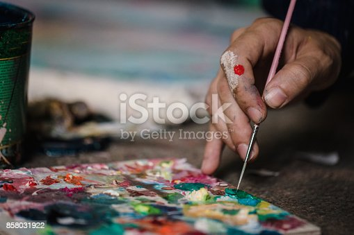 Close-up of an artist- painter working on painting in studio