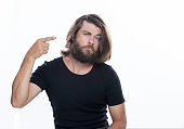istock Look over there. Young handsome man with beard pointing away isolated on white copy space 958339594