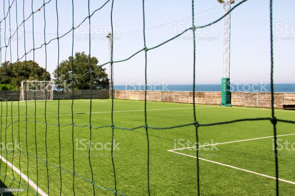 Look through net to empty football field in soccer stadium. Soccer...