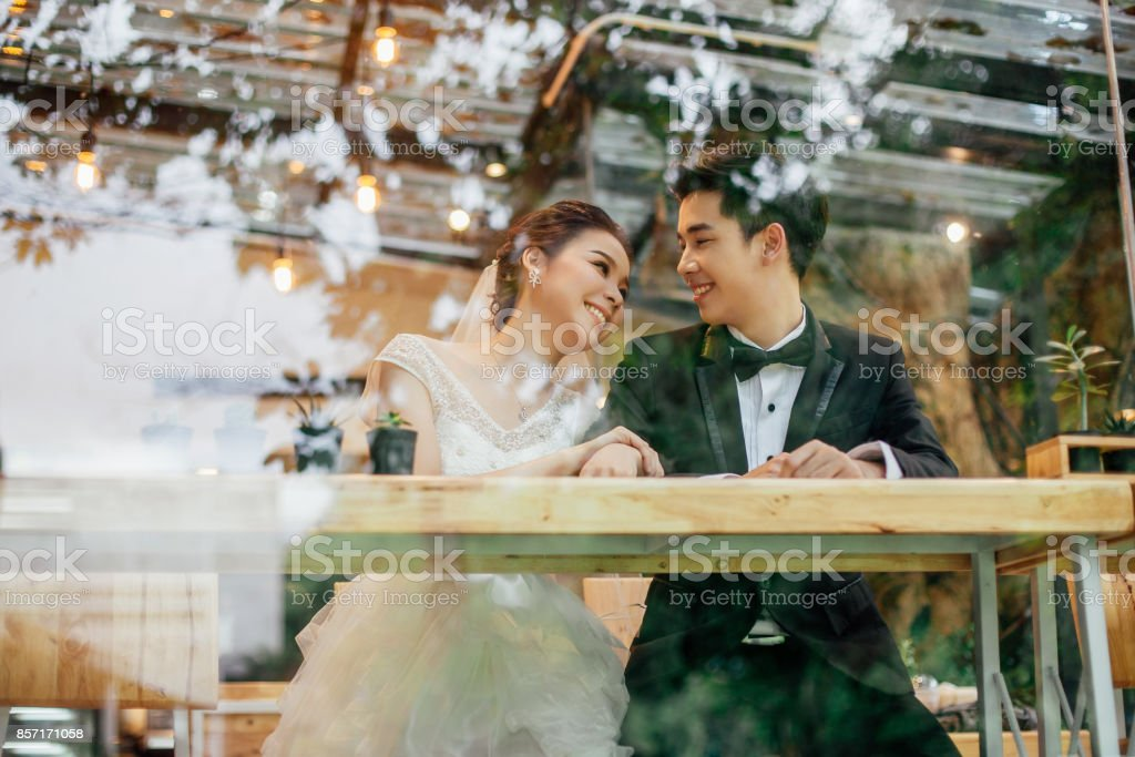 Look through the glass of the restaurant. There is an Asian bride and Asian bride talking together with laughing faces. stock photo