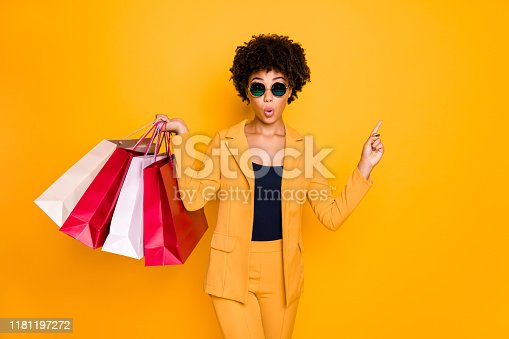 Look unbelievable sale. Amazed brunette wavy hair girl point index finger, copyspace while shopping follow discounts on autumn hold bags wear jacket trousers isolated yellow color background