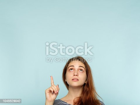 1045527172 istock photo look up advertising above girl point up finger 1045529042