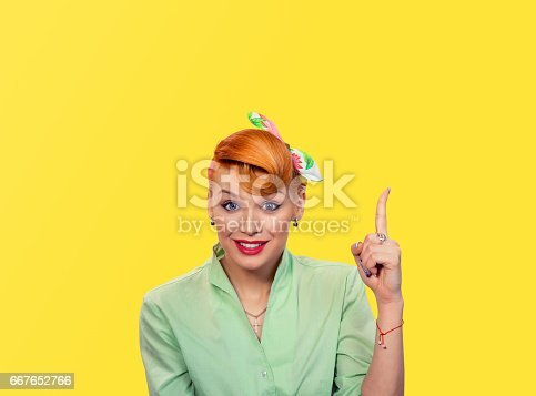 istock Look up here. Closeup red head smart young woman pretty smiling pinup girl green button shirt with idea looking up pointing with finger at blank copy space, retro vintage 50's hairstyle. Body language 667652766