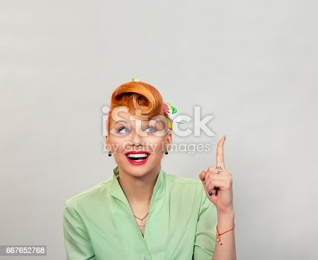 istock Look up here. Closeup red head smart young woman pretty smiling pinup girl green button shirt with idea looking up pointing with finger at blank copy space, retro vintage 50's hairstyle. Body language 667652768