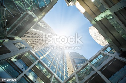 Looking up from the bottom of a high-rise office building in the city, the sun reflects on the building.