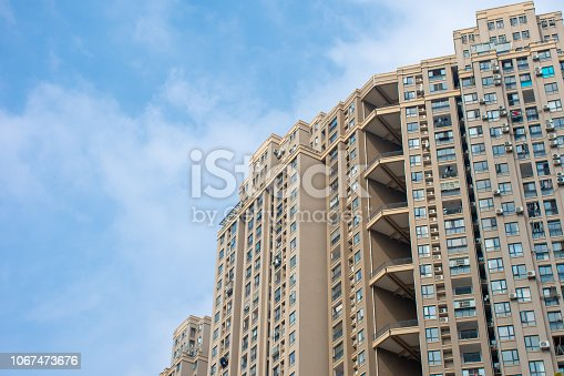 A look up to a newly constructed Chinese apartment with a nice blue sky.