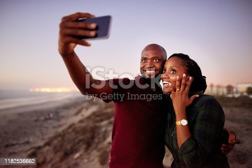 Shot of a loving young couple talking selfie after a marriage proposal at the beach