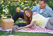 Shot of a married couple feeding a squirrel while enjoying a picnic