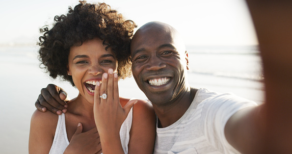Cropped portrait of an affectionate young couple taking selfies on the beach after their engagement