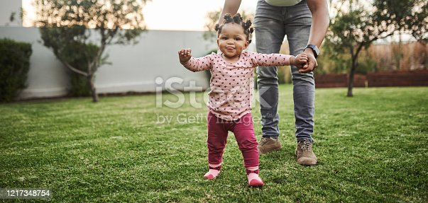 Shot of an adorable baby girl having fun with her dad in their backyard