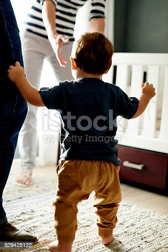 Rearview shot of a little boy taking his first steps with the help of his parents