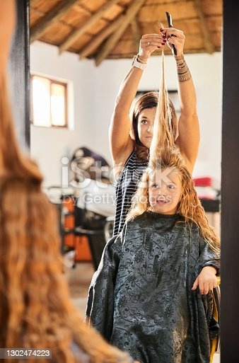 Reflection in mirror of a hairdresser holding hair of a little girl and showing her the length of her hair