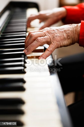 Focus is on the very old, wrinkled and arthritic hands still playing  the piano and making beautiful music!