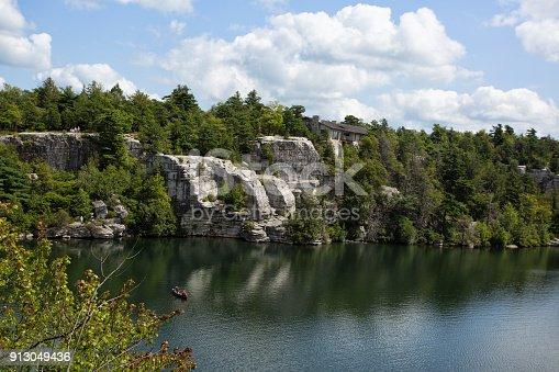 A view of a house on a cliff and a canoe in the water at Lake Minnewaska.