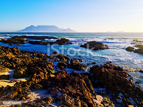 Looking over jagged rocks towards Cape Town and its landmark Table Mountain