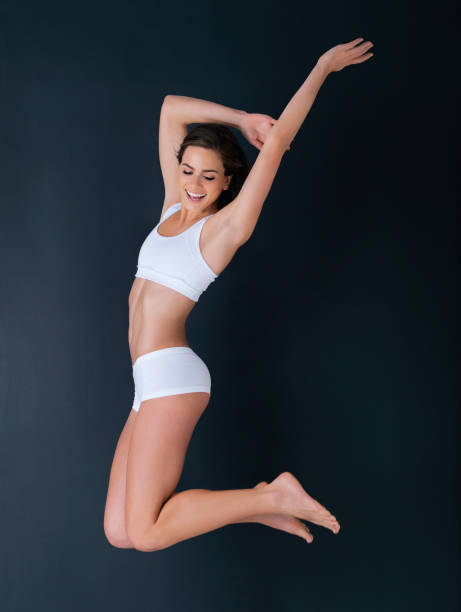 Looking and feeling good Studio shot of a healthy-looking young woman jumping against a dark background lingerie stock pictures, royalty-free photos & images